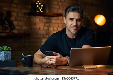 Older white man sitting at desk in dark room at home, working, using phone and tablet