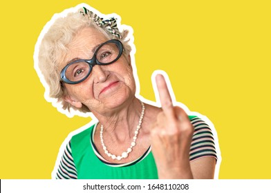 An older woman with an angry facial expression shows fuck you. Isolated The concept of discontent and protest of old woman . Yellow background, stroke.