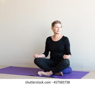 Older woman in black yoga clothing sitting cross legged on purple cushion in meditation posture with hands in guyan mudra