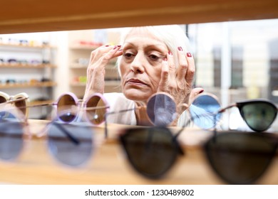 An older woman is buying sunglasses