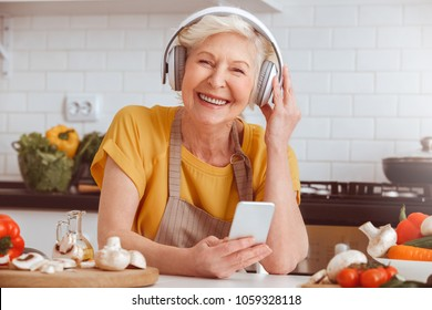 Older woman cooking, listen to music in mobile, toothy smiling