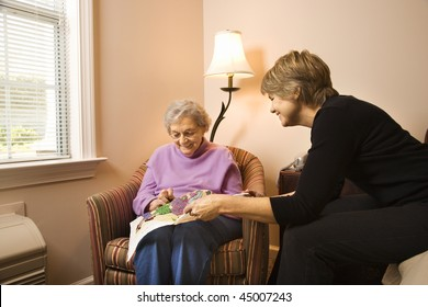 Older woman does needlepoint while another woman watches. Horizontal shot.