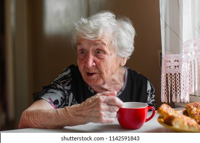 Older woman drinking tea and talking.