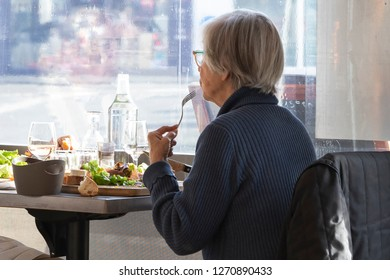 An older woman is eating lunch at a restaurant