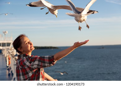 Older woman feeding seagulls. Photo of a middle aged lady standing on the cruise ship deck in a Baltic Sea cruise.