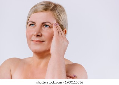 The older woman frowns upward and is unhappy with the wrinkles on her face. White background. Enlarged portrait. Anti-aging, spa and beauty.