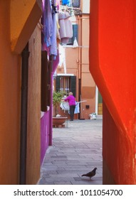 older woman hanging washing to dry in a brightly colored courtyard in burano venice