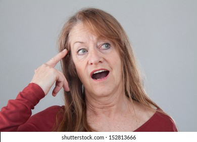 Older woman has an Idea. forefinger on her temporal