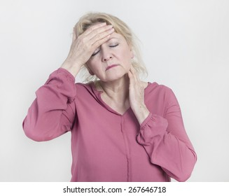 an older woman has pain and holds his head