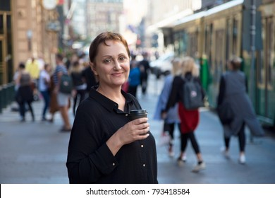 Older woman having coffee/tea. Outdoor headshot of 45 50 year old relaxed woman on lunch break drinking coffee or tea to go. Urban background. Street style shot.