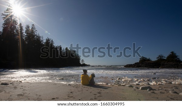 Older woman and her dog sitting on the beach on a bright sunny day with her dog.