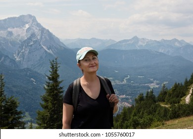 Older woman hiking in the mountains. Mountain hiking and trekking. Hiker on a hiking trail at the mountain peak.