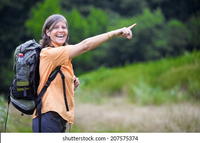 older woman is hiking in nature and pointing to something
