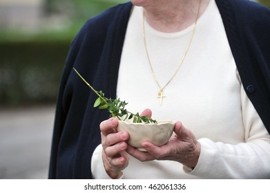 Older woman holding a blessing bowl with a green branch.
