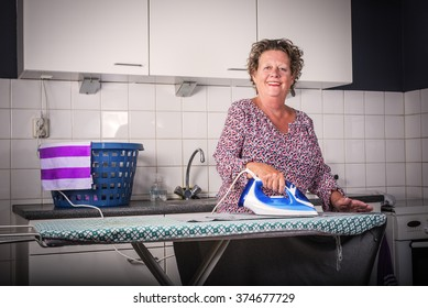 Older woman Ironing clothes. Happy older woman ironing clothes.