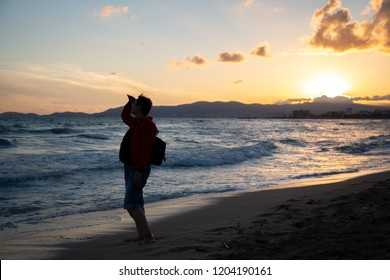 Older woman looking out to sea and enjoying beautiful sunset on a beach.