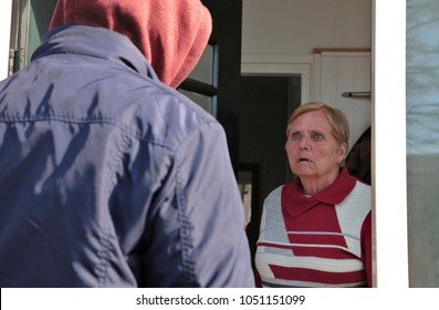 Older woman looks scared at a suspicious person at the door