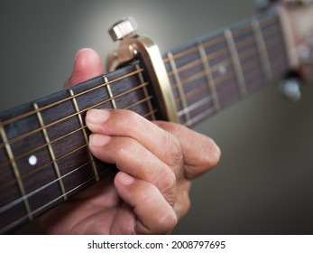 Older woman musician hand holds neck of classic wooden guitar capo on fret 5. Senior female guitarist put fingers on fingerboard playing A minor chord sound Dm. String musical instrument background.