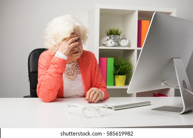 Older woman at the office having headache