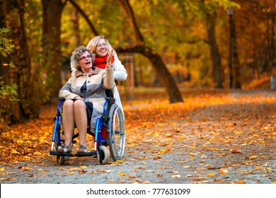 older woman on wheelchair with young woman smiling in the park in autumn