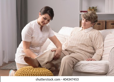 Older woman with painful knee and helpful carer