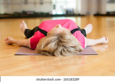 An older woman in a pink yoga outfit rests on the floor of the gym room in savasana (corpse) pose after yoga class,