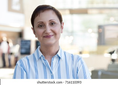 Older woman portrait. Professional head shot of a middle aged 40 50 years old woman wearing white striped shirt in the office / business center /cafe. Blurred background.