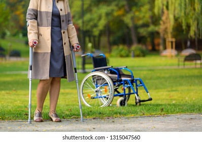 older woman practicing walking on crutches in autumnal park with wheelchair standing in the background