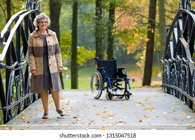 older woman practicing walking without wheelchair in the park
