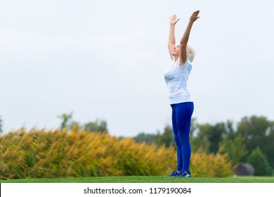 Older woman raising arms for fitness exercise in countryside field with yellow tree leaves in background