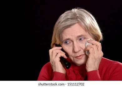 older woman in red crying on a black background