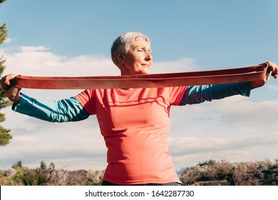 older woman with red t shirt and elastic band practicing sport in the field