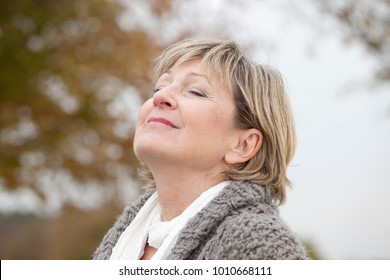 Older woman relaxing outdoors in autumn