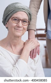 Older woman with scarf with cancer and her daughter holding hand on mother's shoulder