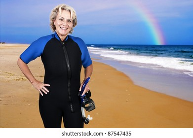 An older woman in scuba wet suit with a mask and snorkel