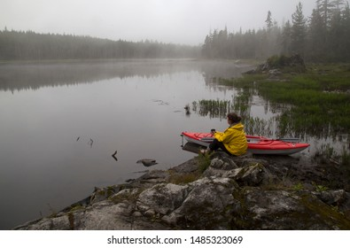 Older woman sitting by her kayak looking out over a foggy, misty lake.