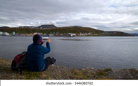 Older woman sitting with her pack taking a tablet picture of Honningsvag Norway.