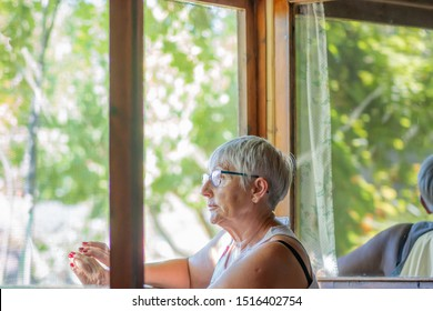 older woman sitting looking out the window at the garden with expression of sadness