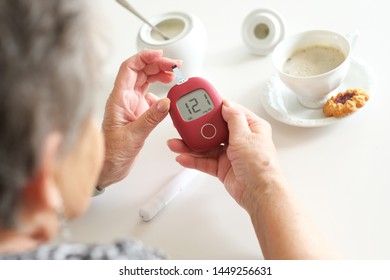 Older woman sitting next to table and examining her glucose level.