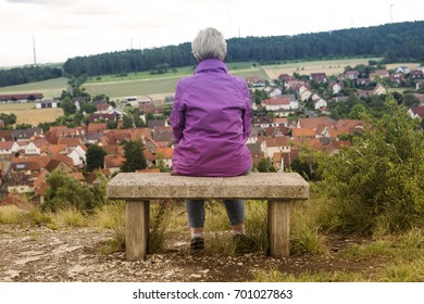 older woman sitting on bench and looking towards a small town