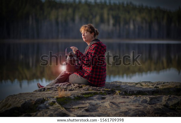 Older woman sitting on a rock by a rural lake.