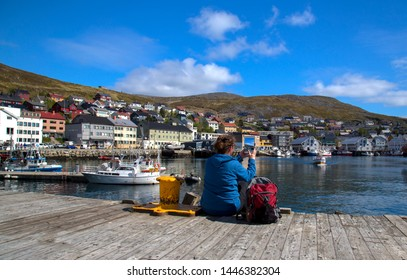 Older woman sitting on a wooden dock in Honningsvag Norway taking a picture with her tablet.