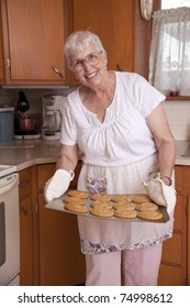 Older woman smiling and holding potholders in her kitchen