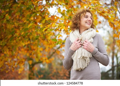 Older woman smiling with yellow leaf background