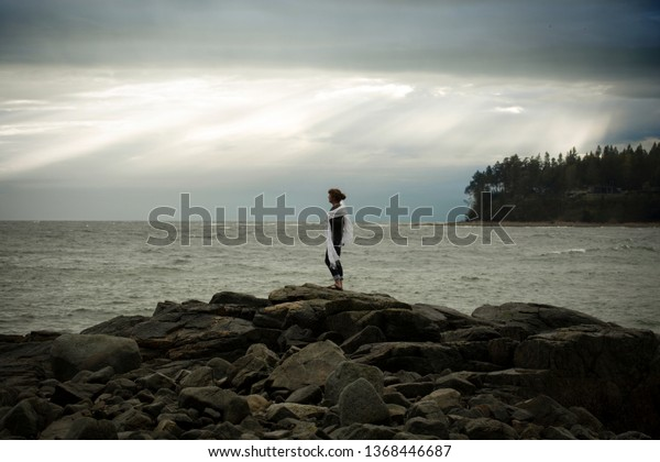 Older woman standing on some rocks over looking the ocean on a stormy day.