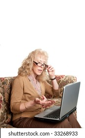 older woman studying finances on a laptop computer