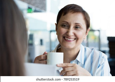 Older woman talking to her colleague or meeting with a business partner or a customer. Portrait of middle aged female having coffee or tea at lunch time in a cafe or business center.