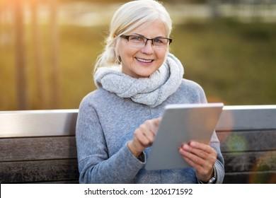 Older woman using digital tablet outdoors