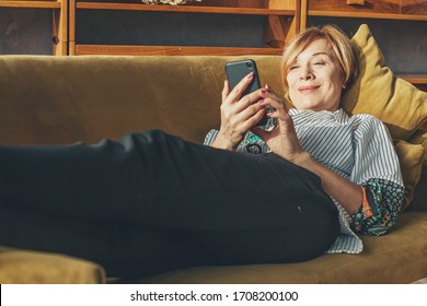 Older woman using smart phone resting at home
