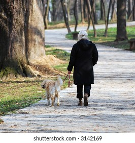 Older woman walking in park with her dog